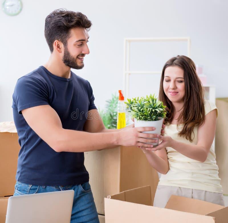 Ung familj packar upp nya hus med lådor arkivfoto