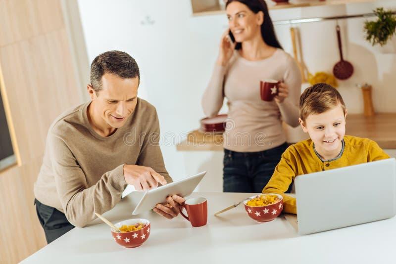 Ung familj som använder deras grejer i stället för att ha frukosten fotografering för bildbyråer