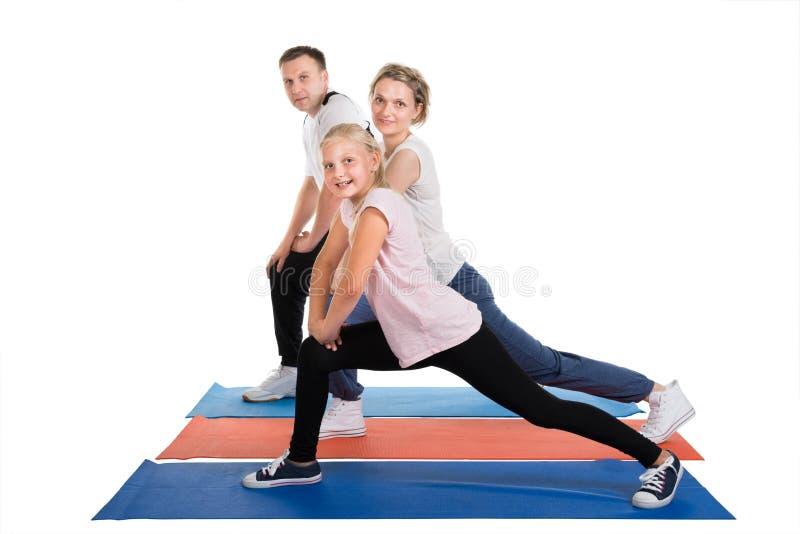 Ung familj som gör sträcka övningar royaltyfri foto