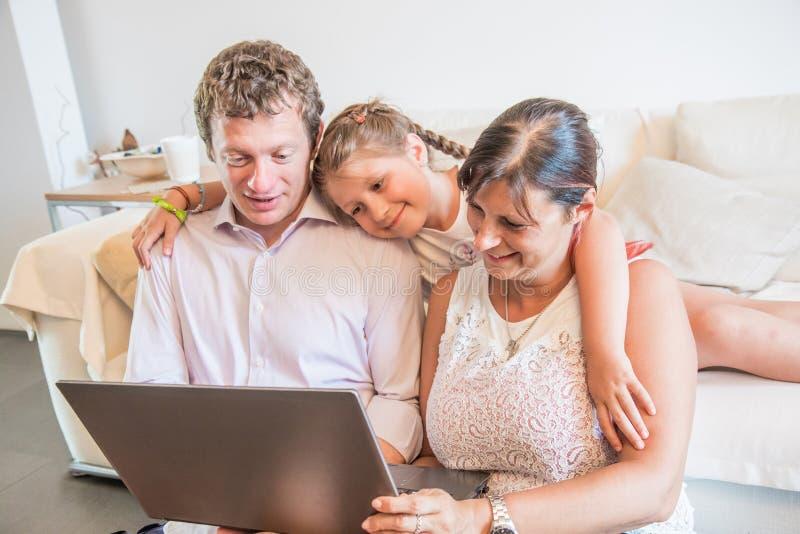 Ung familj som hemma använder bärbara datorn som har den hållande ögonen på videoen för gyckel royaltyfri bild