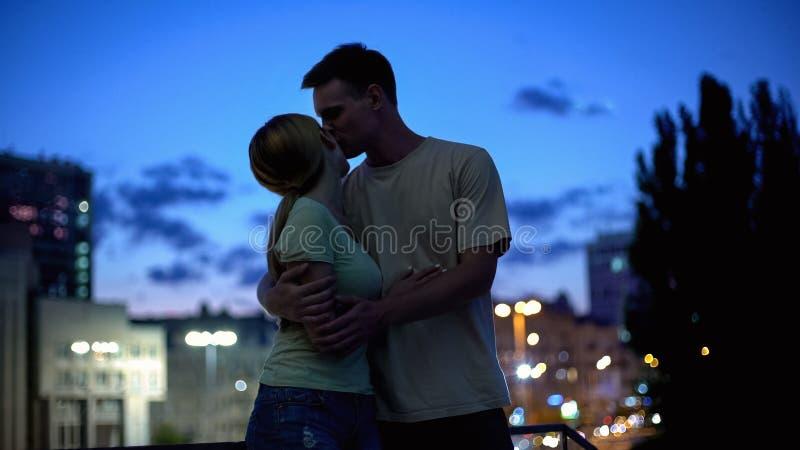 Ung familj som kramar ömt, förtjusande nattstadssikt på bakgrund, förälskelse arkivfoton