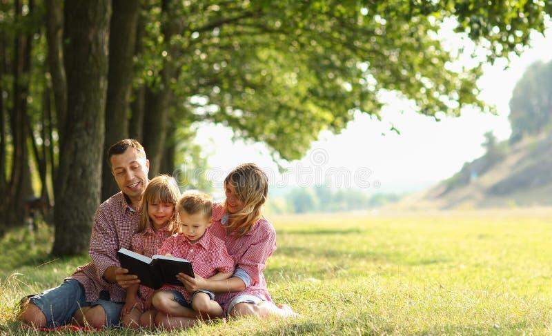 Ung familj som läser bibeln i natur fotografering för bildbyråer