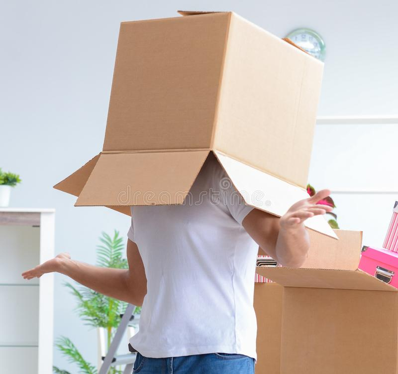 Ung familj som packar upp p? det nya huset med askar royaltyfri fotografi
