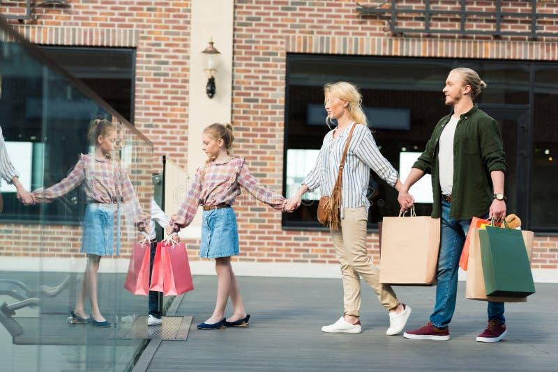 Ung familj som rymmer pappers- påsar och tillsammans går i shoppinggalleria royaltyfri fotografi