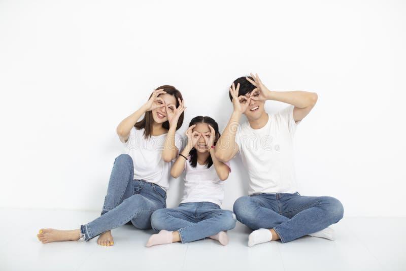 Ung familj som sitter på golvet med en snygg gest royaltyfria bilder