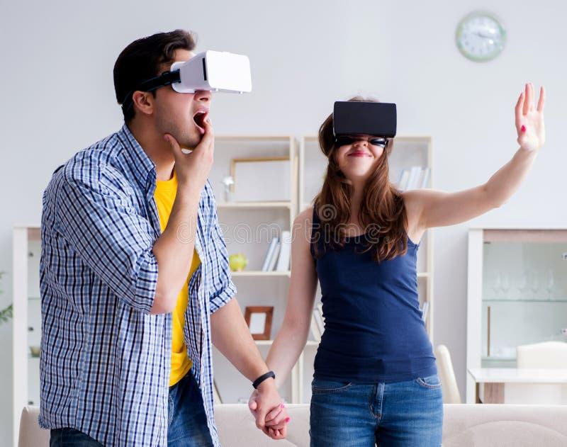 Ung familj som spelar lekar med virtuell verklighetexponeringsglas royaltyfria bilder