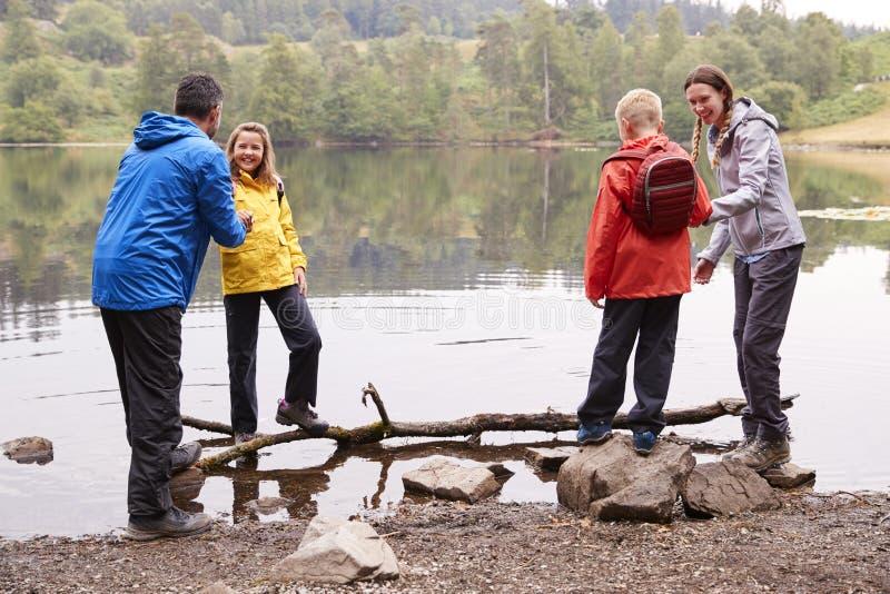 Ung familj som spelar med deras barn på kusten område av för en sjö, sjö, UK royaltyfri fotografi