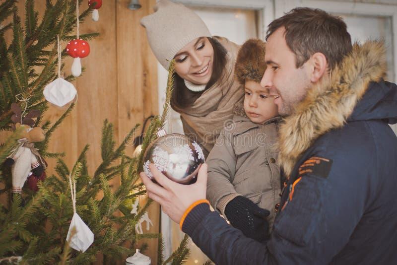 Ung familj som tillsammans tycker om deras ferietid och att dekorera julgrandet fria i varm kläder arkivfoto