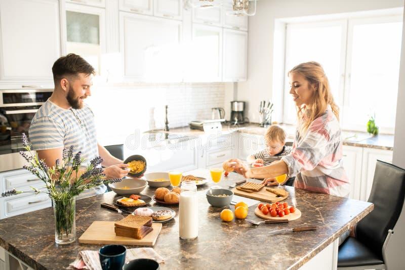 Ung familj som tycker om frukosten i morgon royaltyfri foto