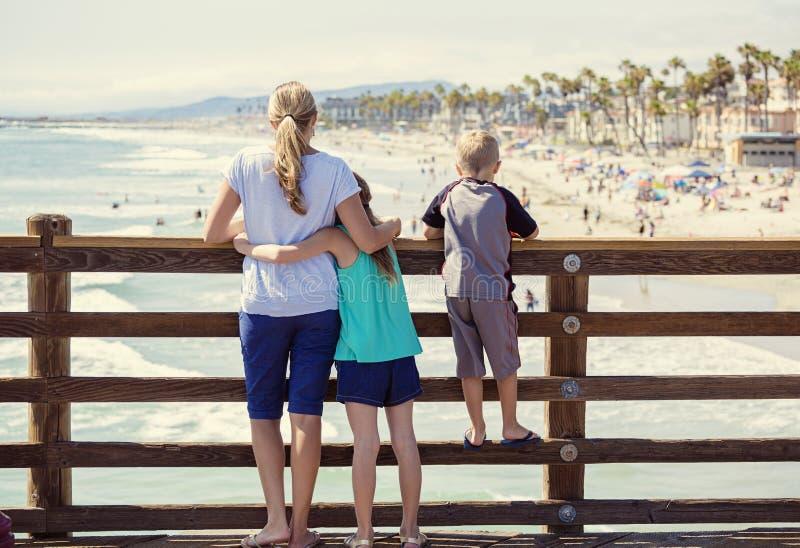 Ung familj som ut hänger på en havpir på semester arkivbild