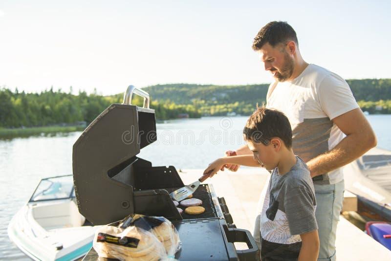 Ung familj som utomhus förbereder hamburgaren på ett galler nästan en sjö fotografering för bildbyråer