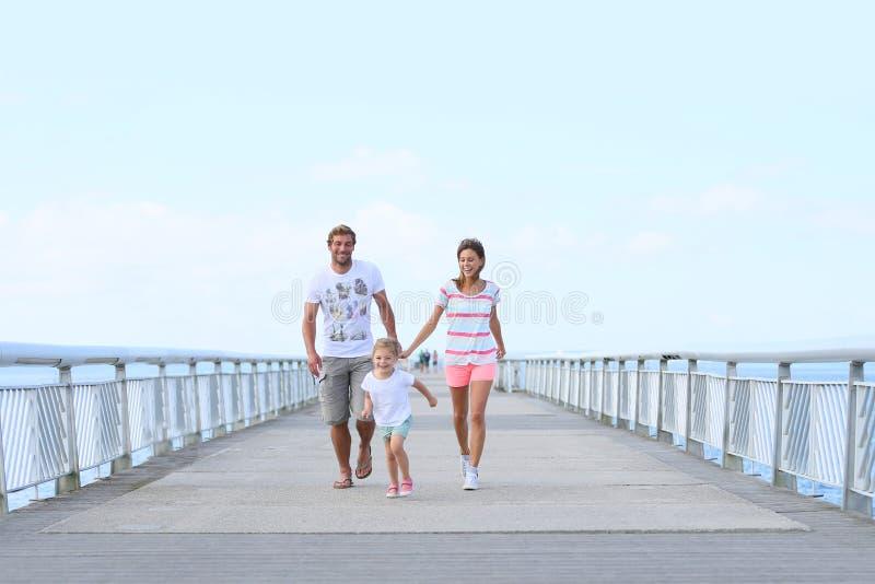 Ung familjspring på bron royaltyfri foto