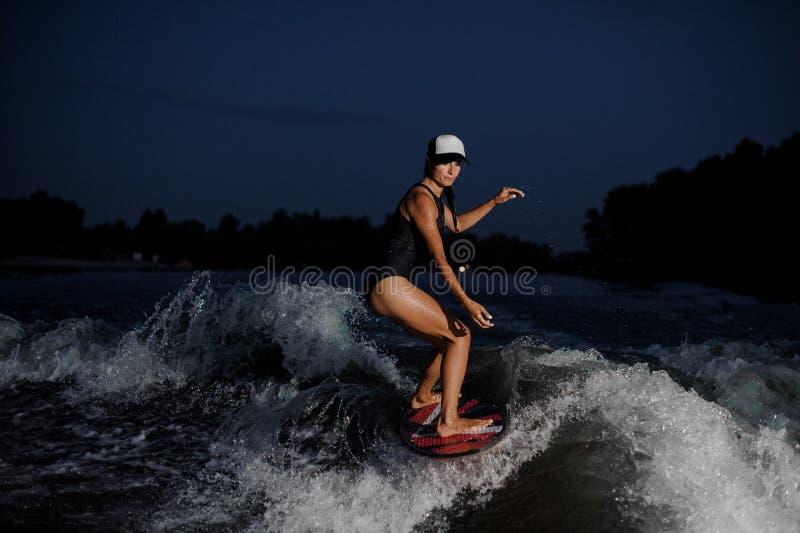 Ung fantastisk flickaridning på den orange wakesurfen i natten royaltyfri foto