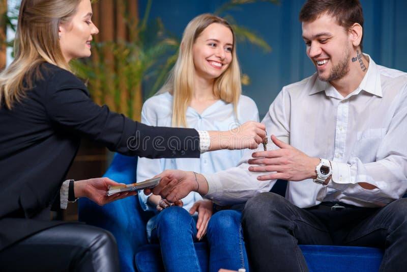 Ung fastighetsmäklare som ger tangent från lägenheten, hus till de unga paren medan manlig klient som ger pengar royaltyfri bild