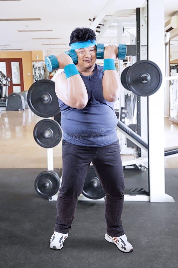 Ung fet man som gör en genomkörare med skivstånger royaltyfri foto