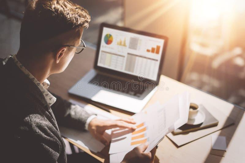 Ung finansmarknadsanalytiker i glasögon som arbetar på det soliga kontoret på bärbara datorn, medan sitta på trätabellen Affärsma