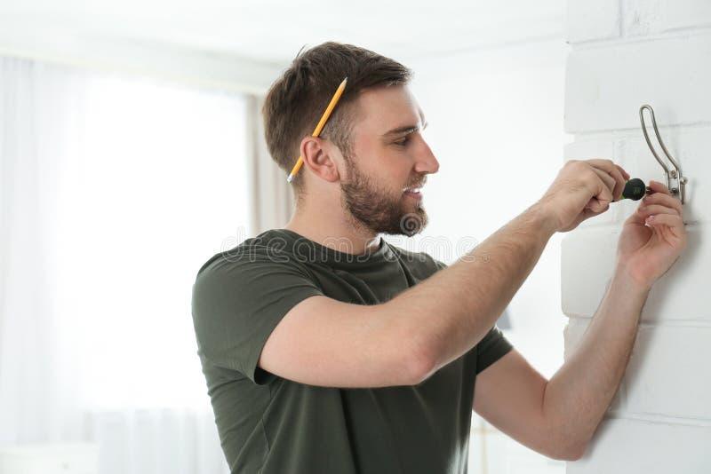 Ung fixandekläder för funktionsduglig man hakar på väggen hemma, utrymme för royaltyfri bild