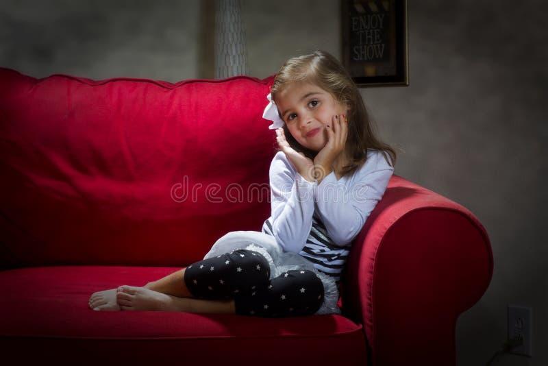 Ung flicka av den röda soffan royaltyfri fotografi