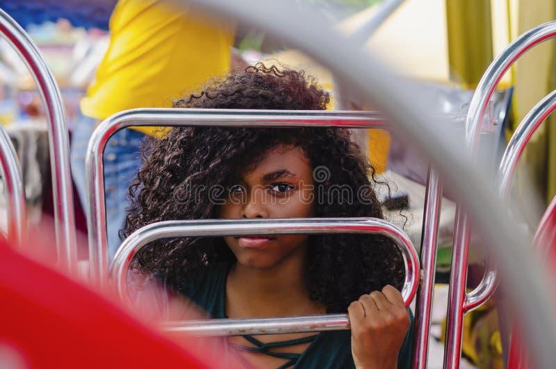 Ung flicka av svart färg och att skratta hår i ferrishjulet som sitter tycka om en sommardag arkivfoton