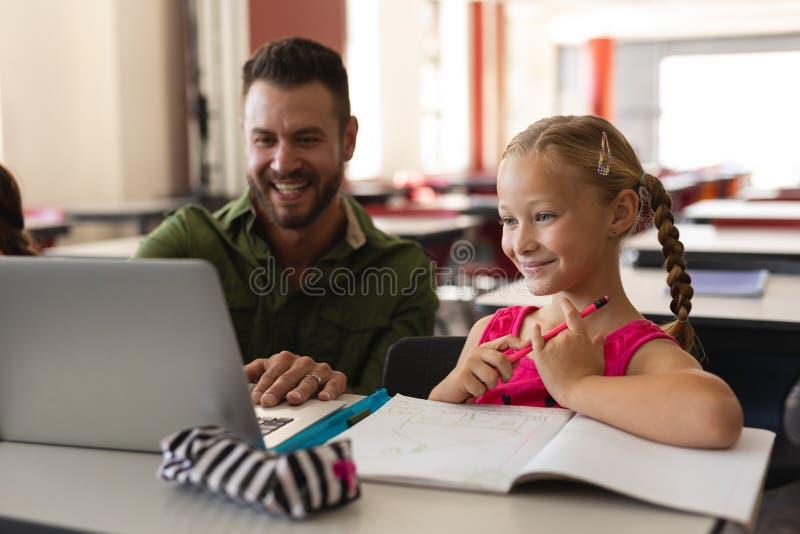 Ung flicka för portion för skolalärare med studien på bärbara datorn i klassrum royaltyfria bilder