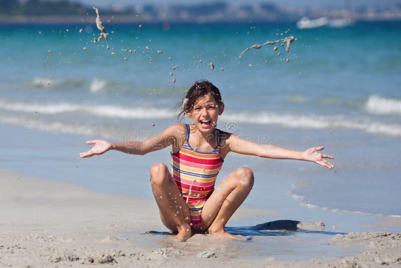 Ung flicka full av glädje på stranden arkivbild