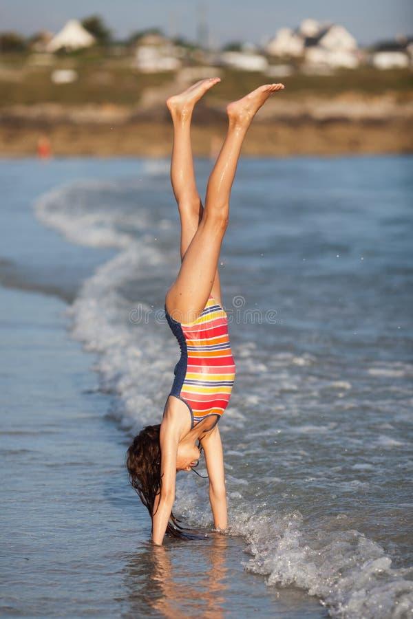 Ung flicka gör en handstans på seafronten royaltyfri foto