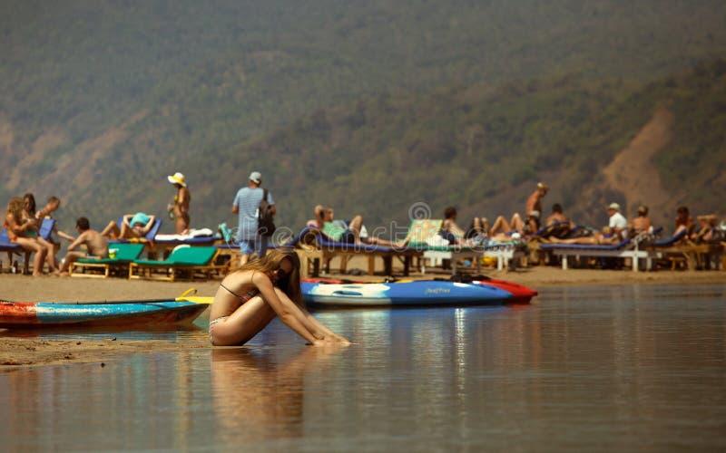 Ung flicka i bikini med den härliga kroppen och solglasögon på stranden royaltyfri bild