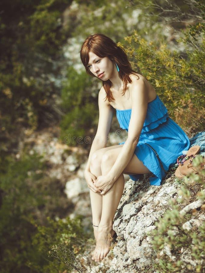 Ung flicka i den ljusa solen i bergen royaltyfria bilder