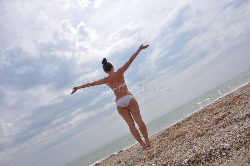 Ung flicka i en bikini som ser havet arkivfoto