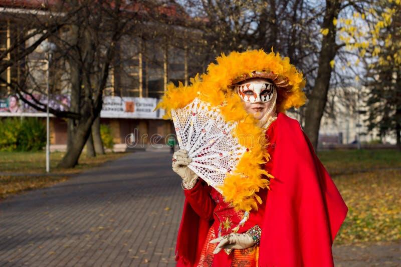 Ung flicka i en ` för dräkt`-höst i en karnevalmaskering royaltyfri foto