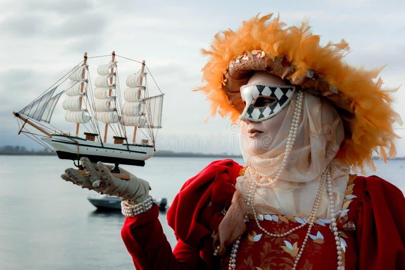 Ung flicka i en ` för dräkt`-höst i en karnevalmaskering arkivfoto