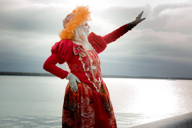 Ung flicka i en ` för dräkt`-höst i en karnevalmaskering royaltyfria bilder