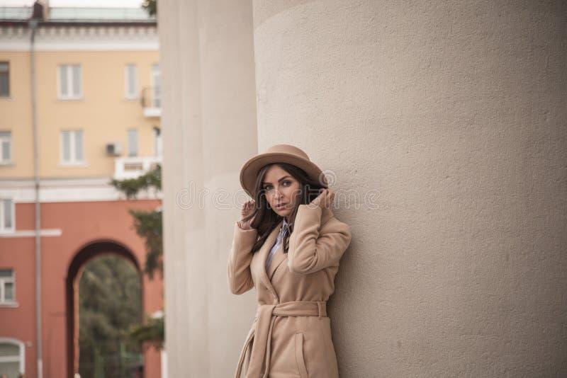 Ung flicka i en hatt och ett lag på bakgrund av teaterkolonner royaltyfri fotografi
