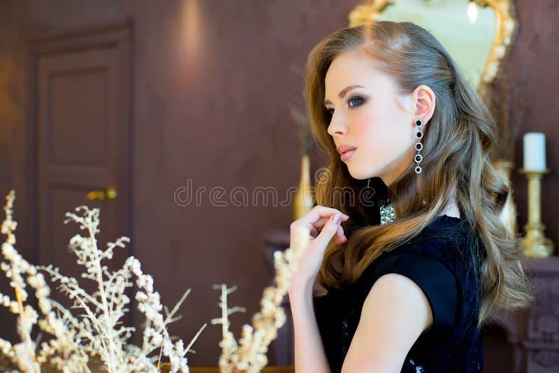 Ung flicka i en svart aftonklänning royaltyfria foton