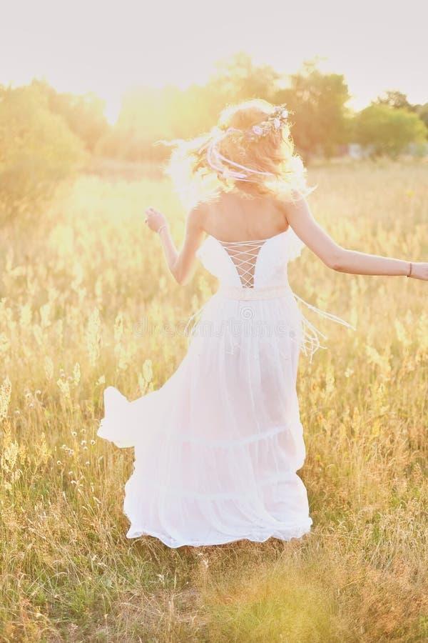 Ung flicka i en vit klänning i ängen Kvinna i en härlig lång klänning som poserar i trädgården Bedöva bruden i en bröllopsklännin arkivfoton