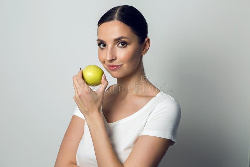 Ung flicka i en vit t-skjorta med ett äpple royaltyfri bild