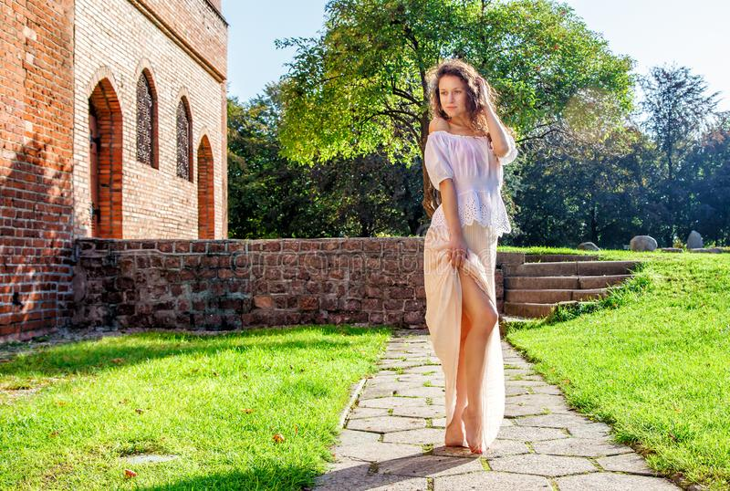 Ung flicka i ett ljust klänninganseende på gränden fotografering för bildbyråer