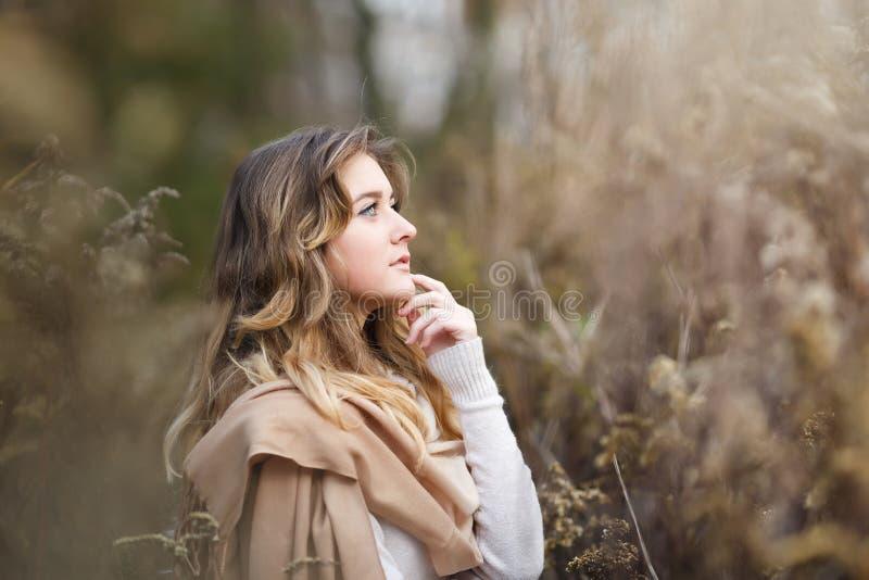Ung flicka i ett torrt gräs arkivfoto