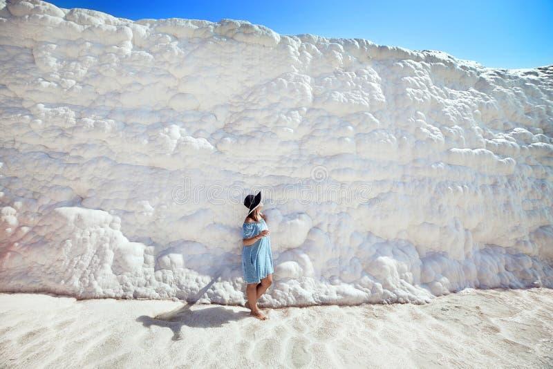Ung flicka i hatten som ser p? travertinetips och terrasser i Pamukkale Bomullsslott i sydv?stliga Turkiet fotografering för bildbyråer
