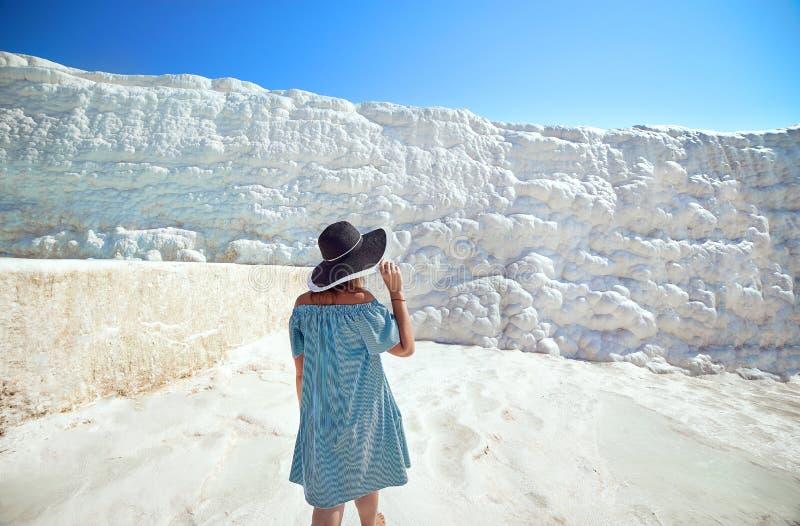 Ung flicka i hatten som ser p? travertinetips och terrasser i Pamukkale Bomullsslott i sydv?stliga Turkiet royaltyfri foto