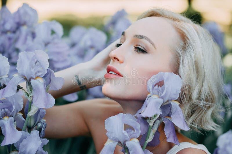 Ung flicka i irisblommor fotografering för bildbyråer