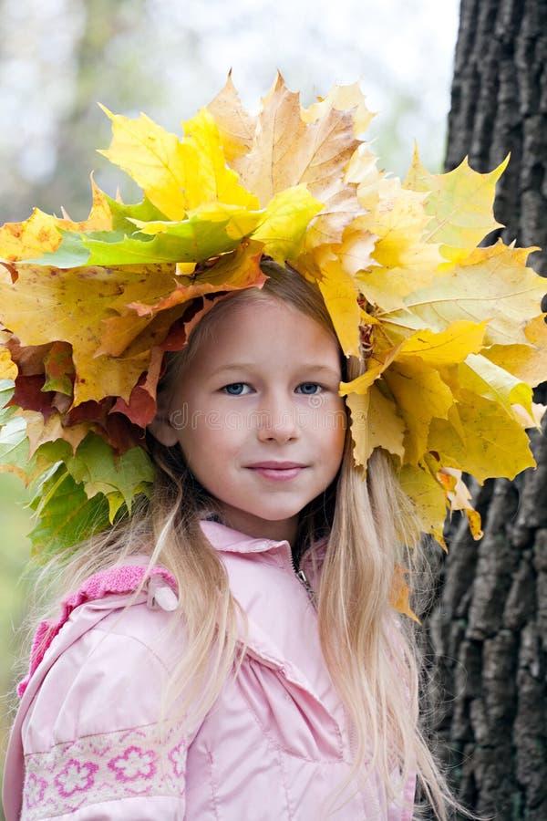 Ung flicka i lönnkrans fotografering för bildbyråer