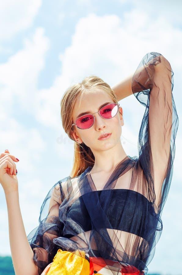 Ung flicka i röd solglasögon som poserar över himmelbakgrund royaltyfria bilder