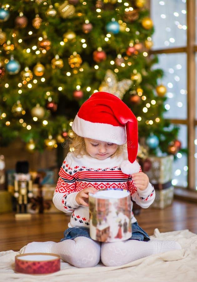 Ung flicka i röda gåvor för jul för santa hattöppning arkivfoto