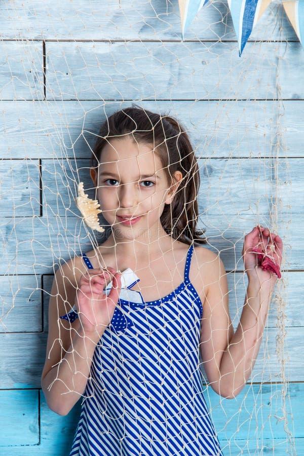 Ung flicka i randig klänning med det marin- nätverket royaltyfri foto