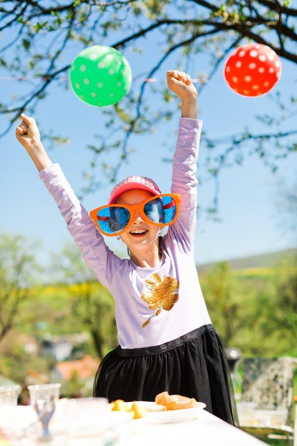 Ung flicka i roliga stora solexponeringsglas på trädgårdpartiet royaltyfri foto