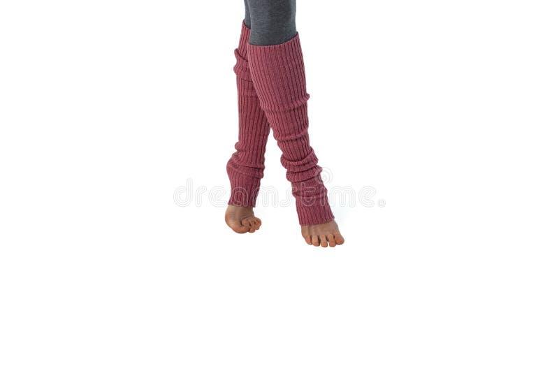 Ung flicka i rosa damasker som är förlovad i pilates som står på fingrar Vit bakgrund arkivfoton