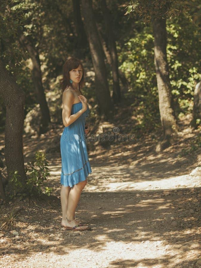 Ung flicka i skuggorna på en bana i skogen arkivfoton