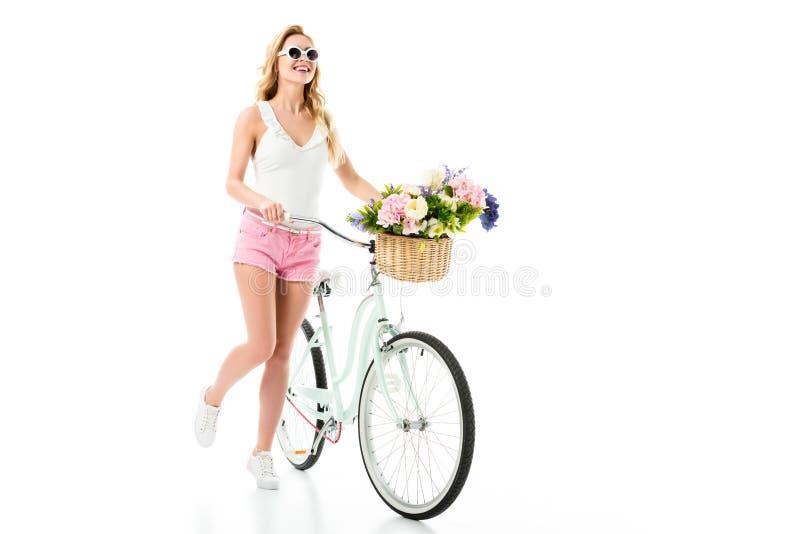 Ung flicka i solglasögon som står med cykeln med blommor i korg royaltyfri fotografi