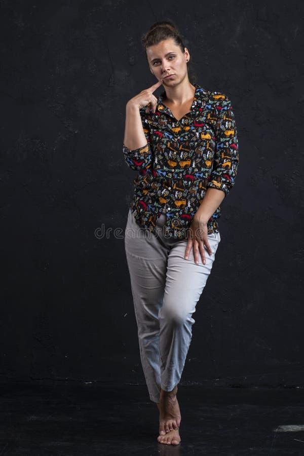 Ung flicka i stilfull kläder som poserar i ramen Attraktiv kvinna i svart skjorta på svart väggbakgrund royaltyfri foto